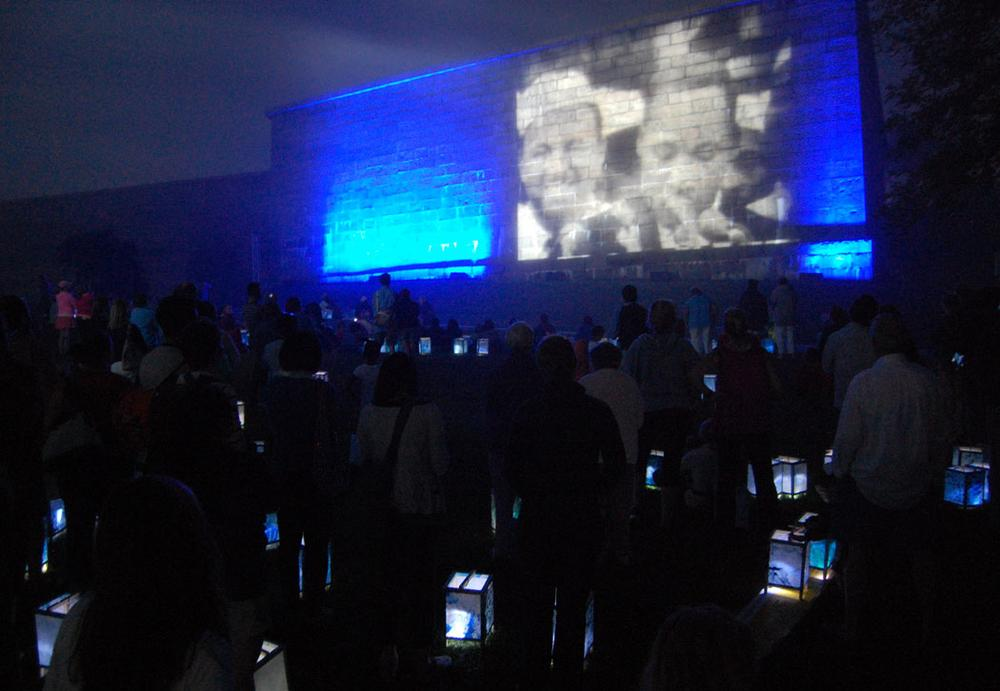 Lanterns glow among the audience watching King's speech projected onto Fort Independence. (Greg Cook)