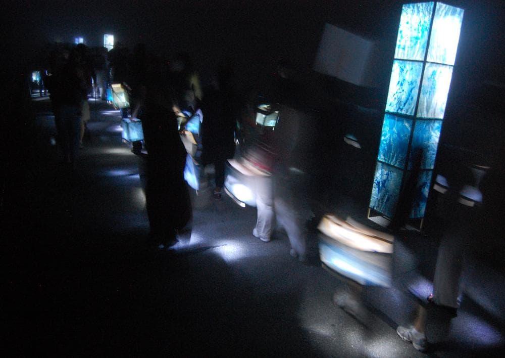 Participants carry lanterns around Pleasure Bay. (Greg Cook)