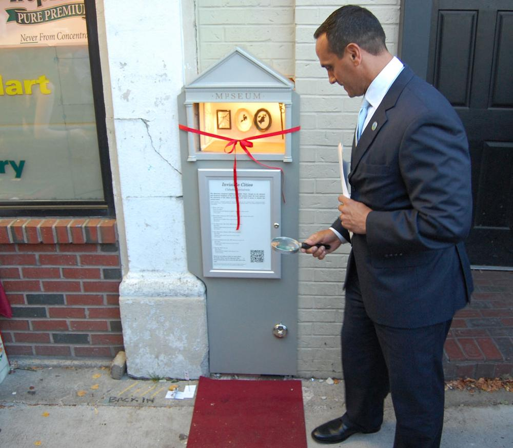 """""""No idea is really too big or too small to hit it big in Somerville,"""" said Mayor Joseph Curtatone, who brought along a magnifying glass to help enjoy the Mµseum. (Greg Cook/WBUR)"""