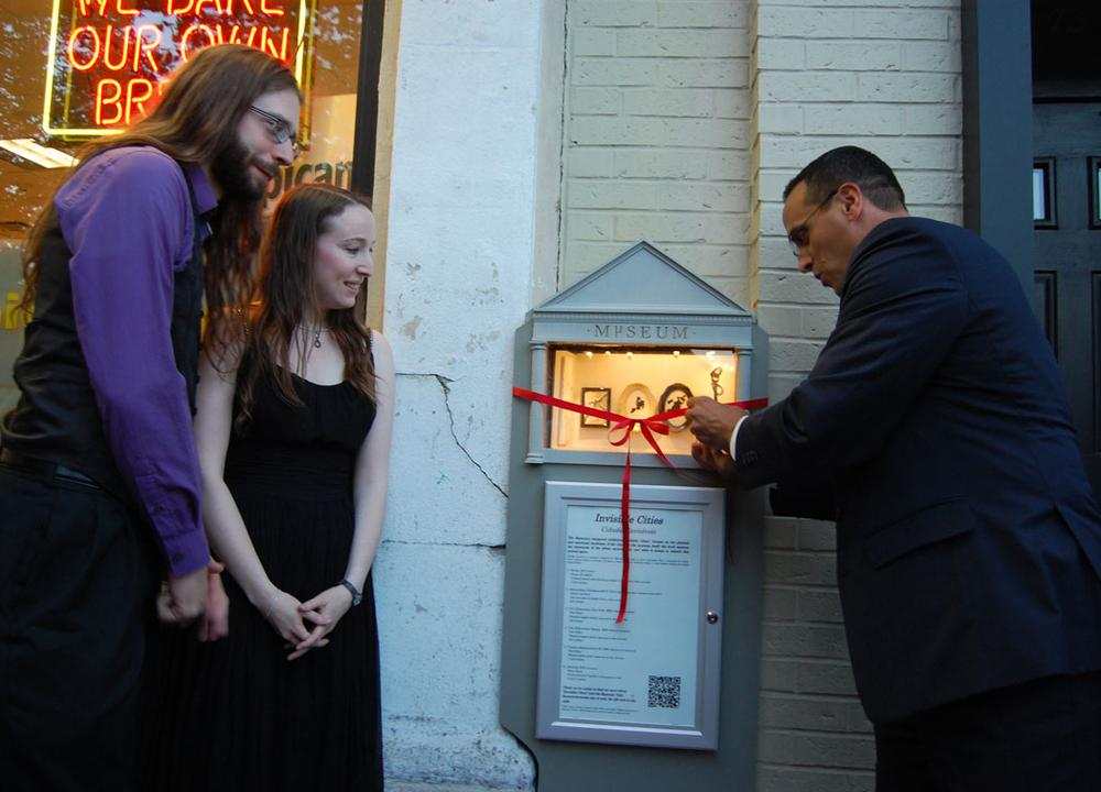 """Somerville Mayor Joseph Curtatone cut the ribbon after giving his """"official micro speech,"""" the entirety of which was: """"Good evening. Thank you."""" (Greg Cook/WBUR)"""