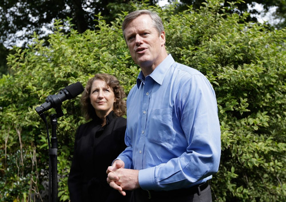 Gubernatorial candidate Charles Baker faces reporters at his Swampscott home Thursday, as his wife Lauren looks on. (Steven Senne/AP)