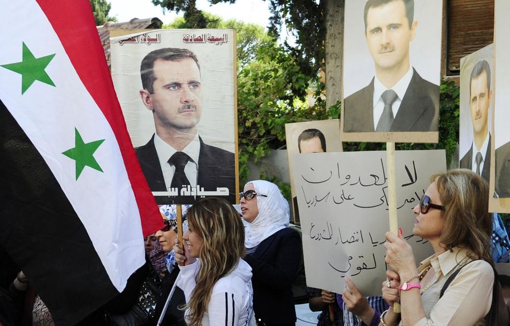 In this photo released by the Syrian official news agency SANA, Syrian, Iraqi, and Palestinian women hold portraits of Syrian President Bashar Assad during a demonstration against the United States considering launching a punitive strike against the Syrian regime, in front of the U.N. headquarters in Damascus, Syria, Wednesday, Sept. 4, 2013. (SANA via AP)