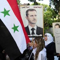 In this photo released by the Syrian official news agency SANA, Syrian, Iraqi, and Palestinian women hold portraits of Syrian President Bashar Assad during a demonstration against the United States considering launching a punitive strike against the Syrian regime, in front of the UN headquarters in Damascus, Syria, Wednesday, Sept. 4, 2013. (SANA via AP)