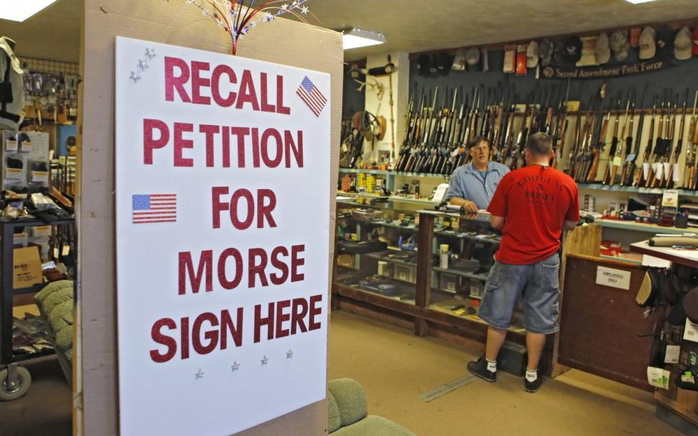 In this photo taken May 24, 2013, a large sign posted at the entrance of Paradise Firearms in Colorado Springs, Colo., invites customers to sign a recall petition against Colorado Democratic State Senate President John Morse. (Ed Andrieski/AP)