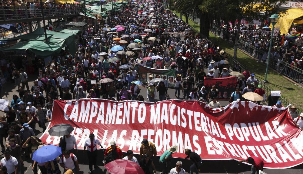 Protesters march down a street in Mexico City, Sunday, Sept. 1, 2013. (Marco Ugarte/AP)