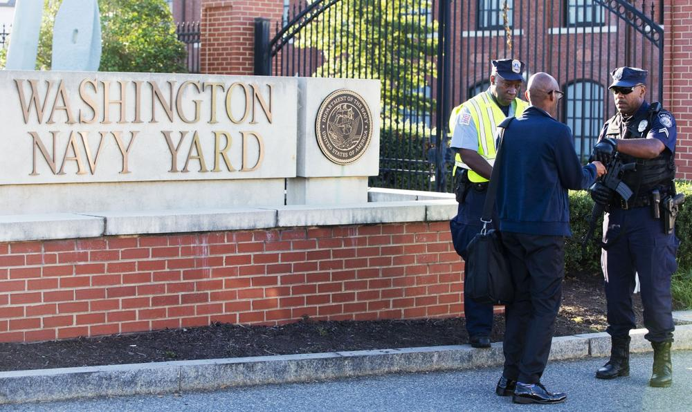 An officer who said he works for the Department of Defense, right, checks an ID outside of the closed Washington Navy Yard in Washington, D.C., on Tuesday, Sept. 17, 2013, the day after a gunman launched an attack there. (Jacquelyn Martin/AP)