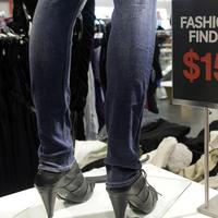 A clerk rearranges a display where sweaters were offered at $15 as part of many day-after-Christmas-only specials offered at H&M retailer on 34th Street in New York. Cost-conscious shoppers haven't just been looking for bargains this season. They've also been more deliberate about when to find those deals. (AP Photo/Kathy Willens)