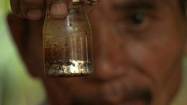 A gold miner in Indonesia holds up a bottle of mercury. (BBC)