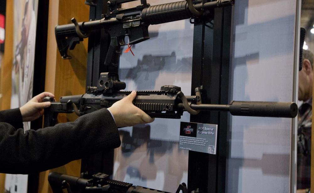 An accessories manufacturer examines a military grade Remington ACR Special Purpose Rifle at a gun show in Las Vegas, January 2013. (Julie Jacobson/AP)