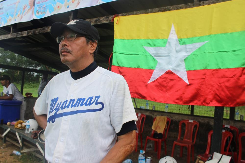 Coach Toru Iwasaki in front of the dugout with the Myanmar national flag. (David Grunebaum/Only A Game)
