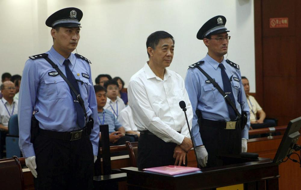 In this Aug. 22, 2013, photo released by the Jinan Intermediate People's Court, former Politburo member and Chongqing city party leader Bo Xilai, center, stands on trial at the court in eastern China's Shandong province. (Jinan Intermediate People's Court via AP)