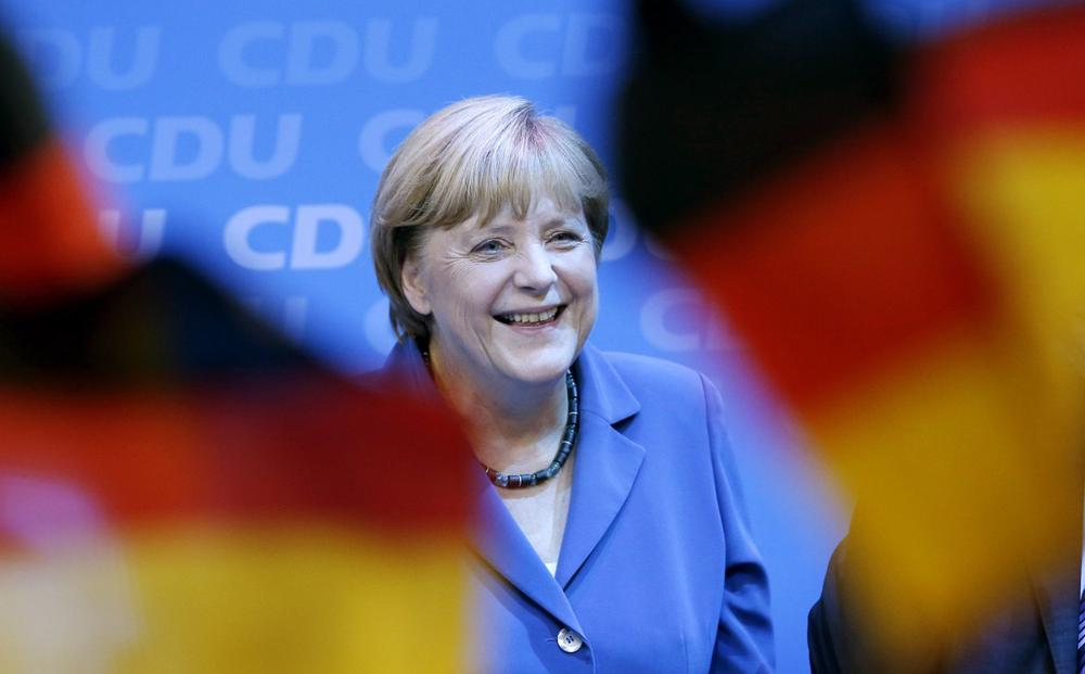 German chancellor Angela Merkel smiles behind German flags at the party headquarters in Berlin, Sunday, Sept. 22, 2013. (Michael Sohn/AP)