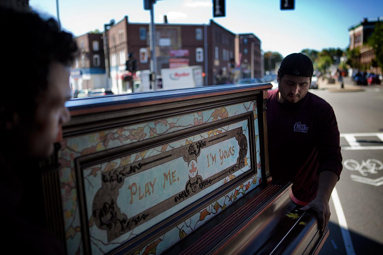 Movers lift artist Pampi's piano from a truck for installation at the Strand Theater in Dorchester. It was inspired by American ragtime. (Jesse Costa/WBUR)