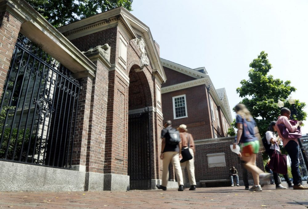 Pedestrians walk through a gate on the campus of Harvard University in Cambridge, Mass. (AP)