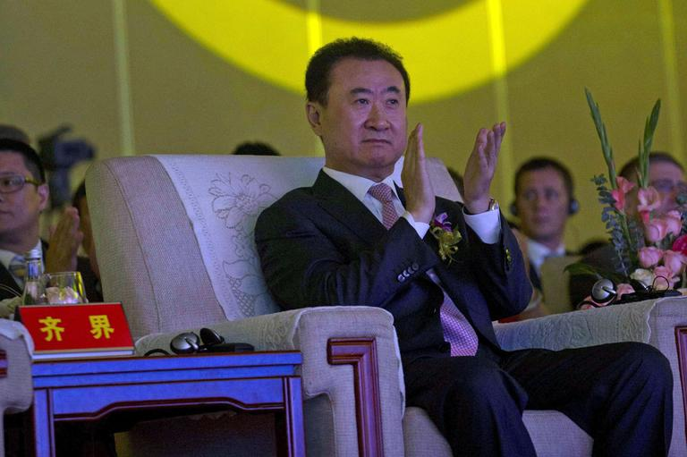 In this Wednesday, June 19, 2013, file photo, Wanda Chairman Wang Jianlin applauds in front of the logo for Dalian Wanda Group during an event at a hotel in Beijing, China. (AP)