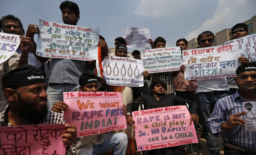 Protesters hold placards outside a court where four men, convicted in the fatal gang rape of a young woman on a moving New Delhi bus last year, are awaiting sentencing, in New Delhi, India, Wednesday, Sept. 11, 2013. (AP Photo/Saurabh Das)