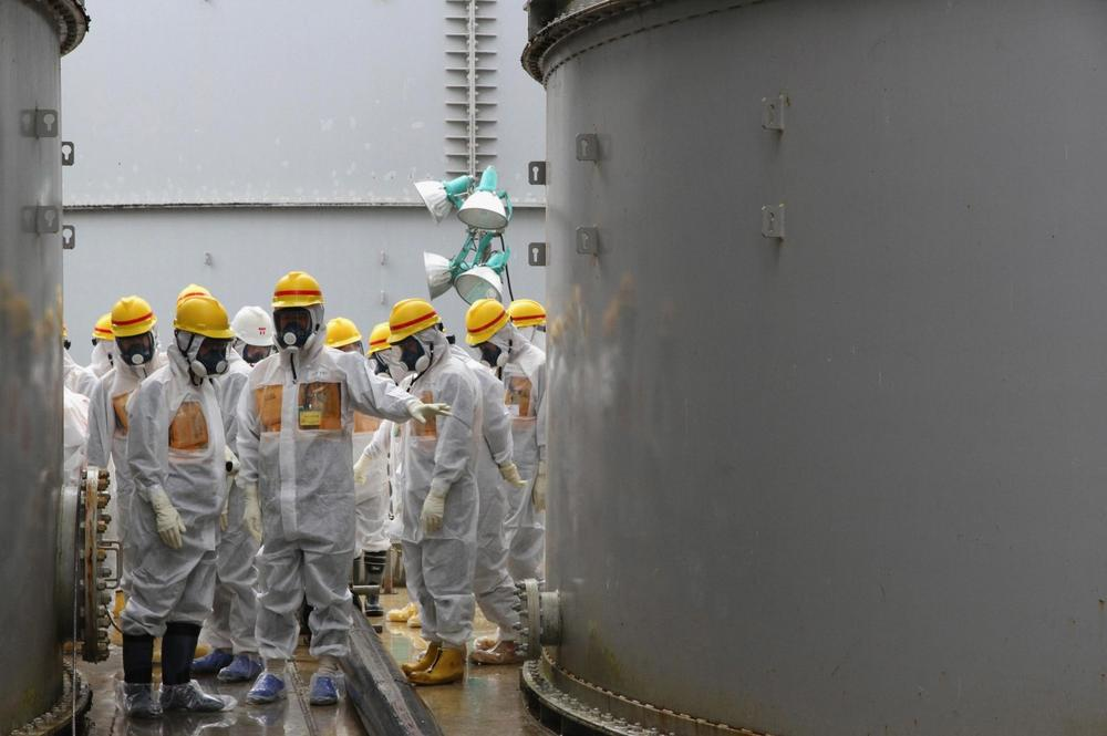 In this photo provided by Nuclear Regulation Authority (NRA), NRA commissioners inspect storage tanks used to contain radioactive water at the Fukushima Dai-ichi nuclear power plant, operated by Tokyo Electric Power Co. (TEPCO), in Okuma in Fukushima prefecture, northern Japan, Friday, Aug. 23, 2013. (AP/Nuclear Regulation Authority)