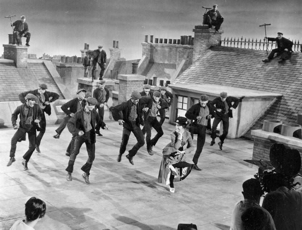 "Actress Julie Andrews dances with the chimney sweeps in the chimney-sweep dance number during filming of ""Mary Poppins"" on a movie set representing London rooftops at the Disney Studios in Hollywood, Ca., Aug. 16, 1963. (AP)"