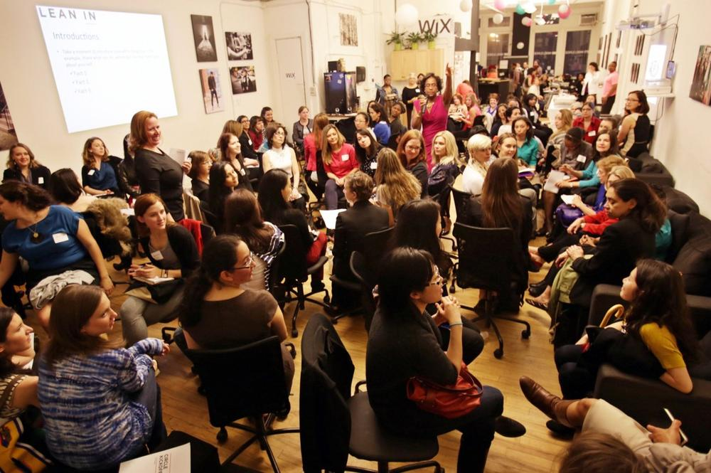"This April 16, 2013 photo provided by Wix Lounge shows group facilitator Franne McNeal, right, standing, and organizer Mary Dove, standing left, addressing women at a ""Lean In"" meeting in New York. The group is inspired by Facebook COO Sheryl Sandberg's book ""Lean In"" which seeks to empower women in the workplace. (AP Photo/Wix Lounge, Galo Delgado)"