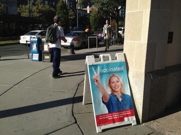 An ad for flu vaccines outside a Brookline, Mass., pharmacy on Sept. 20, 2013. (Carey Goldberg/WBUR)