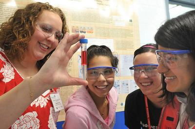 Teacher Heather Scott and students Stephanie Lamas, Dana Bielinski and Smriti Marwaha examine a test tube at Science Careers in Search of Women, hosted by the U.S. Department of Energy's Argonne National Laboratory. (Argonne National Laboratory)
