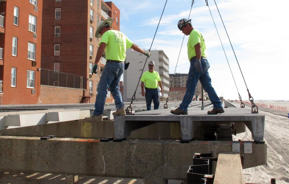 Workers prepare to attach a new section of the boardwalk in Long Beach, N.Y., Oct. 3, 2013, where the entire 2.2 mile long boardwalk had to be replaced after it was damaged in Superstorm Sandy. (Frank Eltman/AP)