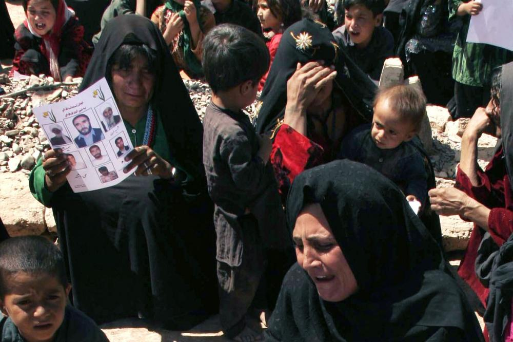 Afghan women mourn on Sept. 9, 2008 over the graves of their family members, unseen, who were killed on August 22, 2008 during a U.S. led raid in Azizabad village. (Fraidoon Pooyaa/AP)
