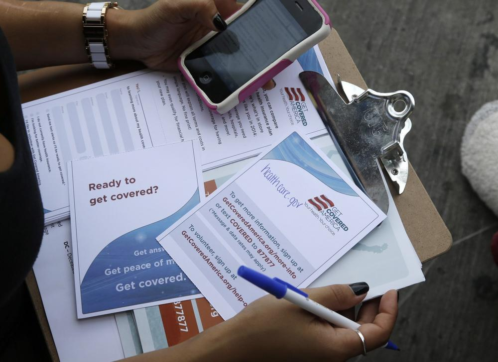 Maygan Rollins, 22, a field organizer with Enroll America, holds a clipboard with pamphlets while canvassing at a bus stop, Wednesday, Sept. 25, 2013, in Miami. (Lynne Sladky/AP)