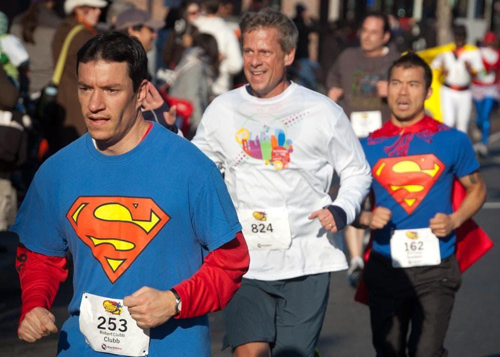 Supermen run along Massachusetts Avenue. (Greg Cook)