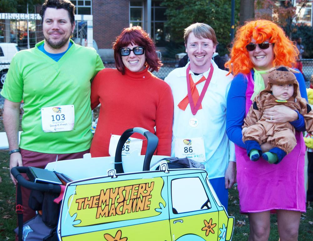 """""""Last year we ran as Ghostbusters. I was the Stay Puft Marshmallow Man,"""" says Doug Rooney of Watertown (far left). """"I was chasing him,"""" says Tara Pottebaum (far right). At the end of the race, Rooney's sister waited with a ring—and Rooney asked Pottebaum to marry him. They arrived to this year's run in Scooby-Doo costumes—including the couple's five-month old son Orion as Scooby himself. They're thinking of getting married next year. (Greg Cook)"""