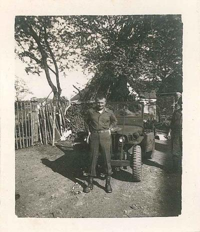 Raymond Allen Ashlock stands in front of a Jeep in Czechoslovakia.