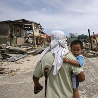 A man walks home with his son Monday Nov. 11, 2013 following Friday's devastating typhoon that lashed Hernani township, Eastern Samar province, central Philippines. (Bullit Marquez/AP)