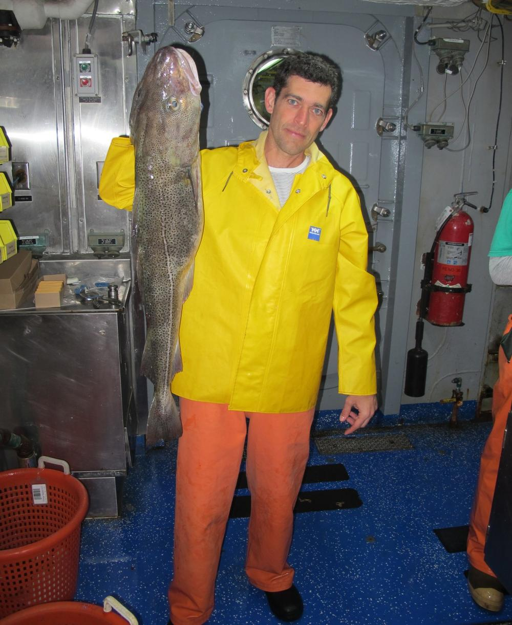 """Rowan Jacobsen holds up a cod fish. Pictured above is a monkfish, one of the """"trash fish"""" species that sustainable fisheries advocates say consumers should be eating more of now that cod is depleted. (Rowan Jacobsen)"""