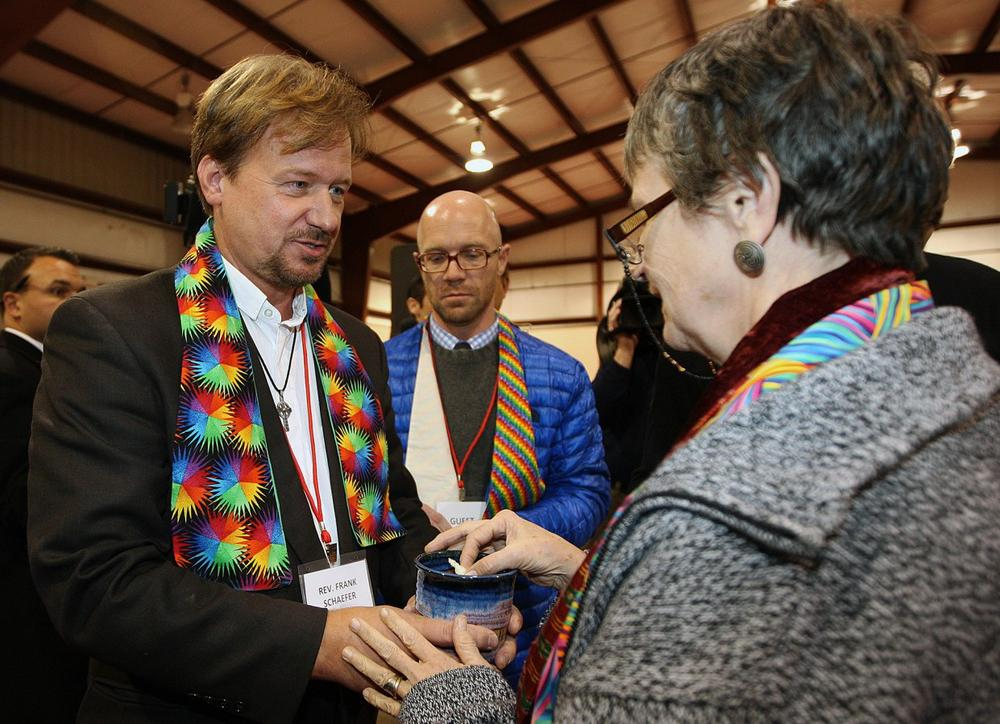 The Rev. Frank Schaefer, left, of Lebanon Pa., celebrates communion with supporters after the sentencing phase of the trial at Camp Innabah, a United Methodist retreat, in Spring City Pa. Tuesday Nov. 19, 2013. (Chris Knight/AP)