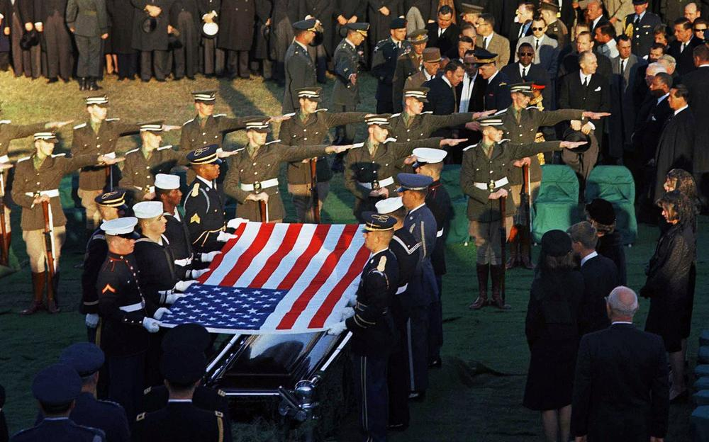 The Irish cadet honor guard, center rows with arms outstretched, stand in formation as the U.S. flag is lifted from the coffin of President John F. Kennedy during his funeral services at Arlington National Cemetery in Arlington, Va., Nov. 25, 1963. (AP)