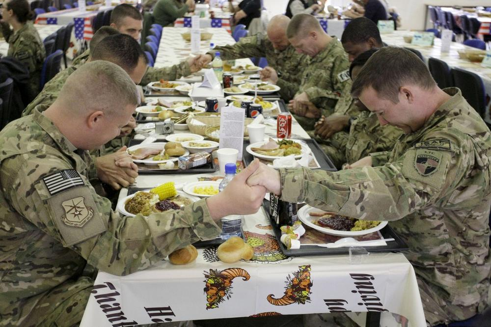 U.S. soldiers pray before eating a Thanksgiving meal at a dining hall at the U.S.-led coalition base in Kabul, Afghanistan, Thursday, Nov. 22, 2012. (Musadeq Sadeq/AP)