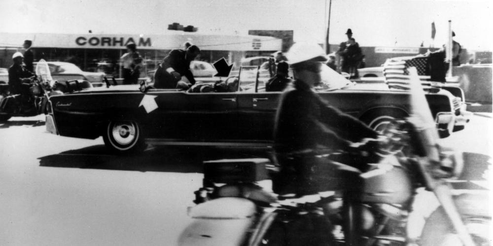Secret Service agent Clint Hill climbs into the back seat of the limousine a moment after President John F. Kennedy and Gov. John Connally of Texas were shot in Dallas, Nov. 22, 1963. Black arrow points to Mrs. Connally ducking bullets, and white arrow points out the agent's foot, mistakenly thought to be the president's when the photo first ran.(AP)