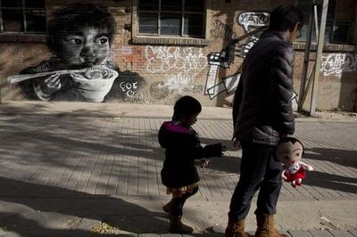 A woman leads a child while holding a doll as they walk near mural depicting a child eating in Beijing Sunday, Nov. 17, 2013. Experts estimate that the first easing of the country's strict one-child policy in three decades announced this month allowing couples where one partner is an only child to have a second baby will result in 1 million to 2 million extra births per year in the first few years, on top of the 16 million babies born annually in China. (AP)