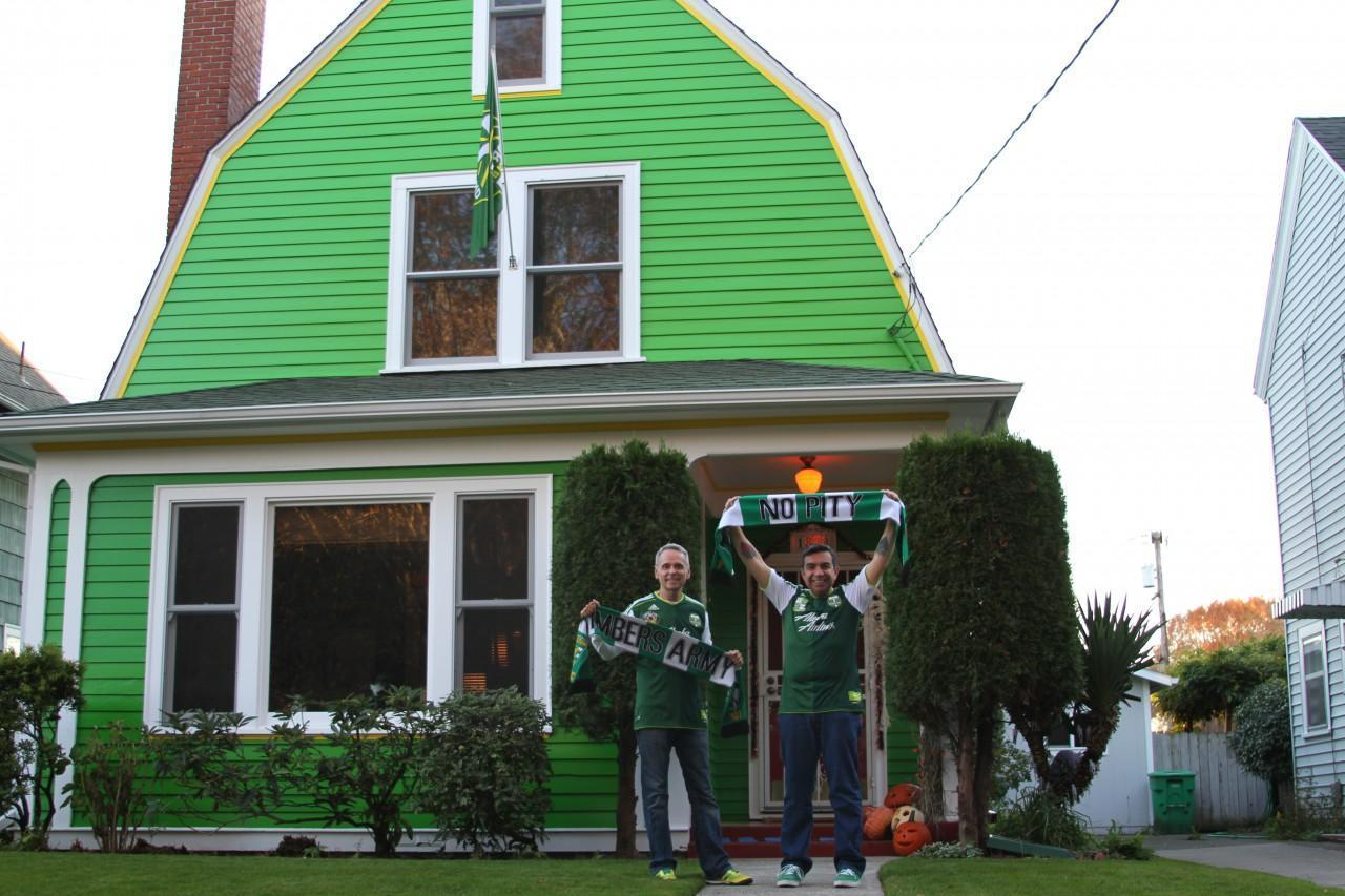 "John Halseth (left) and Robin Castro live in Northeast Portland. The couple's so enthusiastic about the Portland Timbers that they painted their house ""Timbers' green."" (Conrad Wilson/Only A Game)"