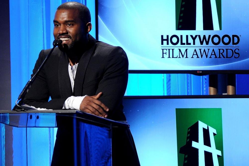 "In this Tuesday, Oct. 22, 2013 file photo, recording artist Kanye West speaks onstage during the 17th Annual Hollywood Film Awards Gala at the Beverly Hilton Hotel in Beverly Hills, Calif. West is postponing the rest of his ""Yeezus"" tour after a 60-foot LED screen used during his shows was damaged. The use of the Confederate flag on his tour merchandise has stirred controversy. (AP)"