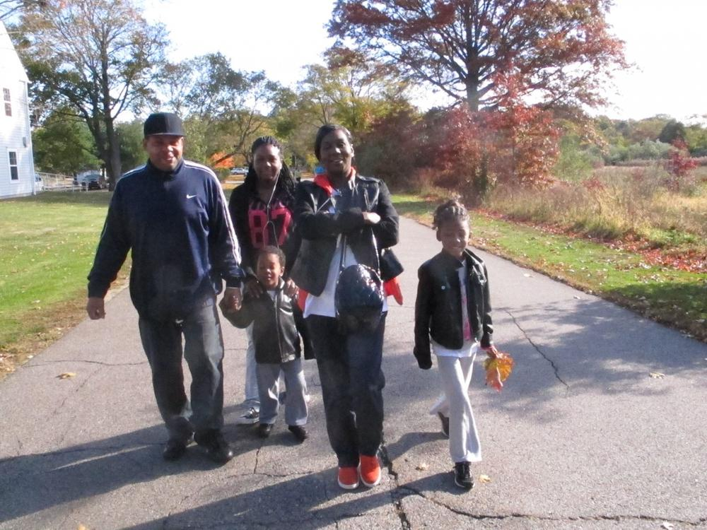 Melody Salhudin (right) leads her family on a walk through Cushing Park in Framingham. (Martha Bebinger/WBUR)