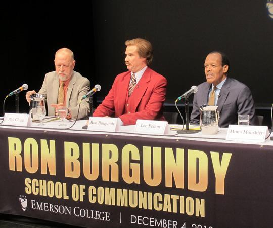 "Will Ferrell speaks at a press conference as his character from ""Anchorman,"" Ron Burgundy. Emerson's president, Lee Pelton, is right, while the interim dean of Emerson's School of Communication, Phillip Glenn, is left. (Andrea Shea/WBUR)"