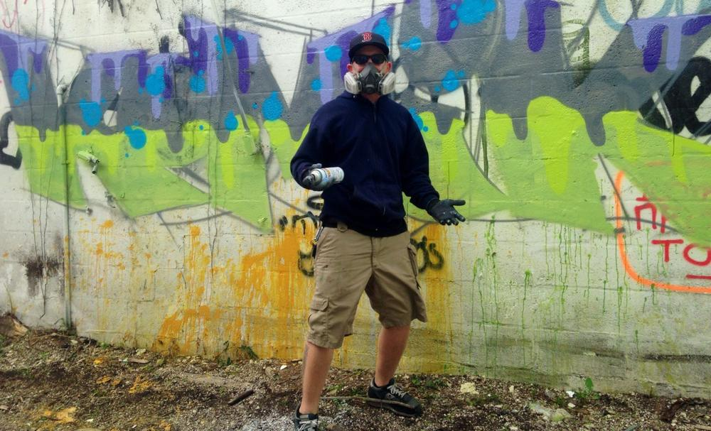 Street artist Komik in front of his piece. (Julia Duba/WLRN)