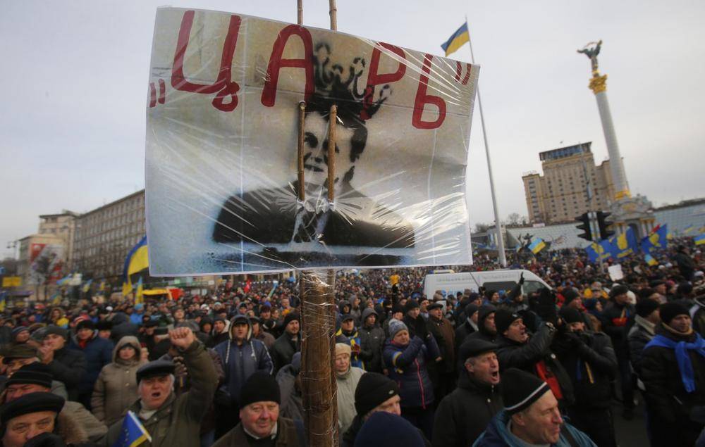 """Protesters hold a placard with a portrait of President Viktor Yanukovych and reading """"Tsar"""" as they rally at the central Independence square in Kiev, Ukraine, on Tuesday, Dec. 3, 2013. (Sergei Grits/AP)"""