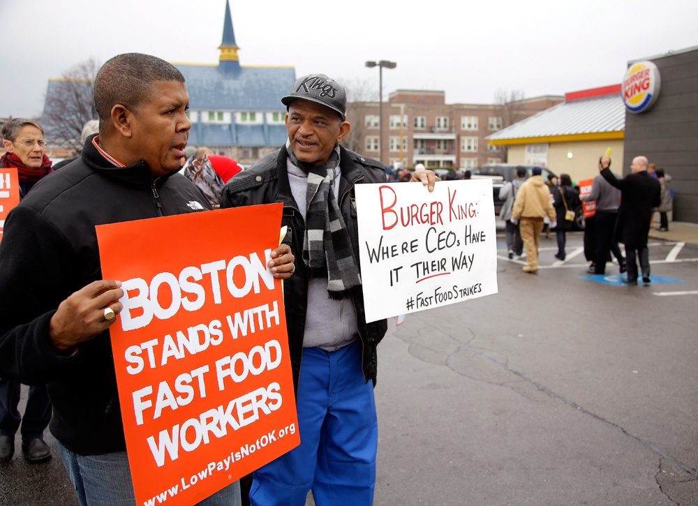 Pedro Rodriguez, right, talks with Andrus Reyes at a Burger King in Boston's Dorchester neighborhood in December, as part of nationwide protests in support of higher wages for workers in the fast-food industry and other minimum-wage jobs. (Stephan Savoia/AP)