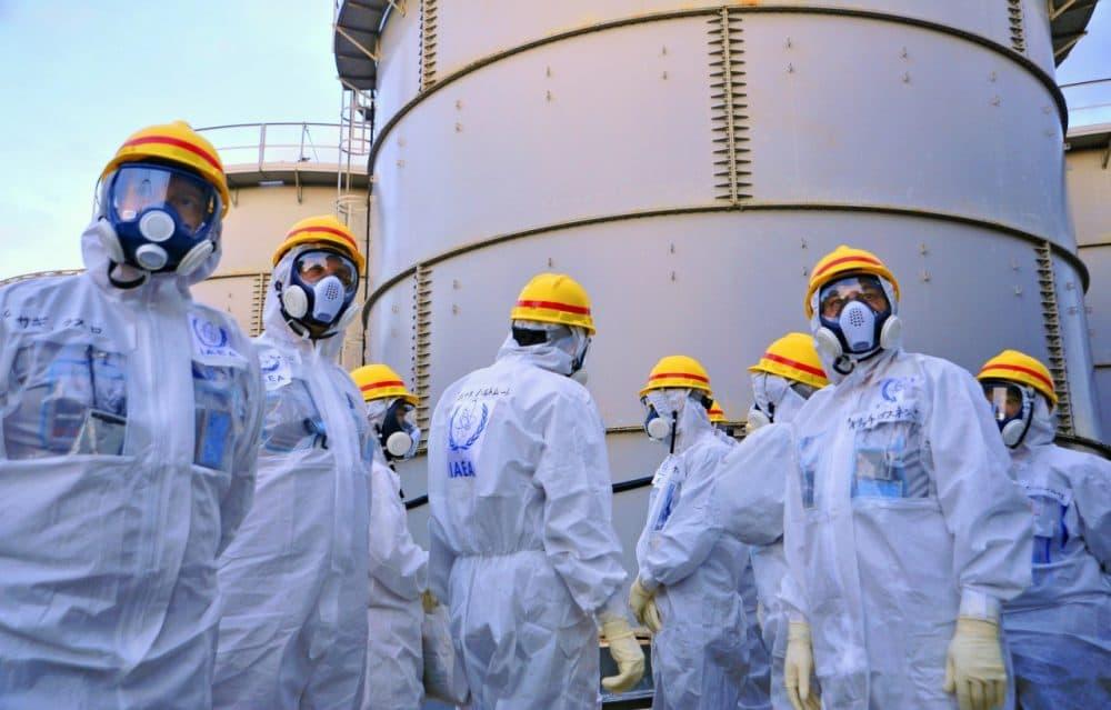 A team of experts with the International Atomic Energy Agency (IAEA) check out water storage tanks at the crippled Fukushima Dai-ichi nuclear power plant in Okuma, Japan, Nov. 27, 2013. (Greg Webb/IAEA)