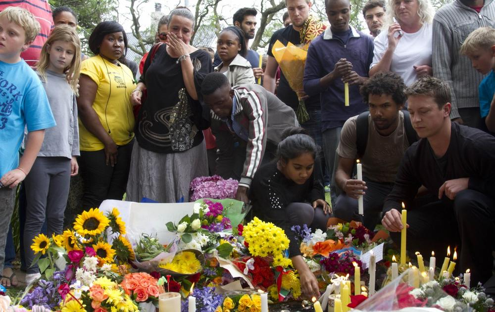 Mourners lay floral and candle tributes to former South African president Nelson Mandela outside his Johannesburg home, Friday, Dec. 6, 2013. (Athol Moralee/AP)
