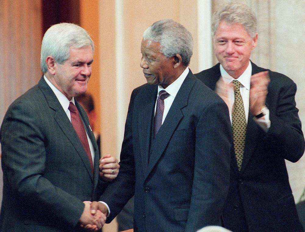 South African President Nelson Mandela shakes hands with U.S. Speaker of the House Newt Gingrich, as U.S. President Bill Clinton looks on during ceremonies September 23, 1998, in which Mandela received the Congressional Gold Medal on Capitol Hill in Washington, D.C. (William Philpott/AFP/Getty Images)