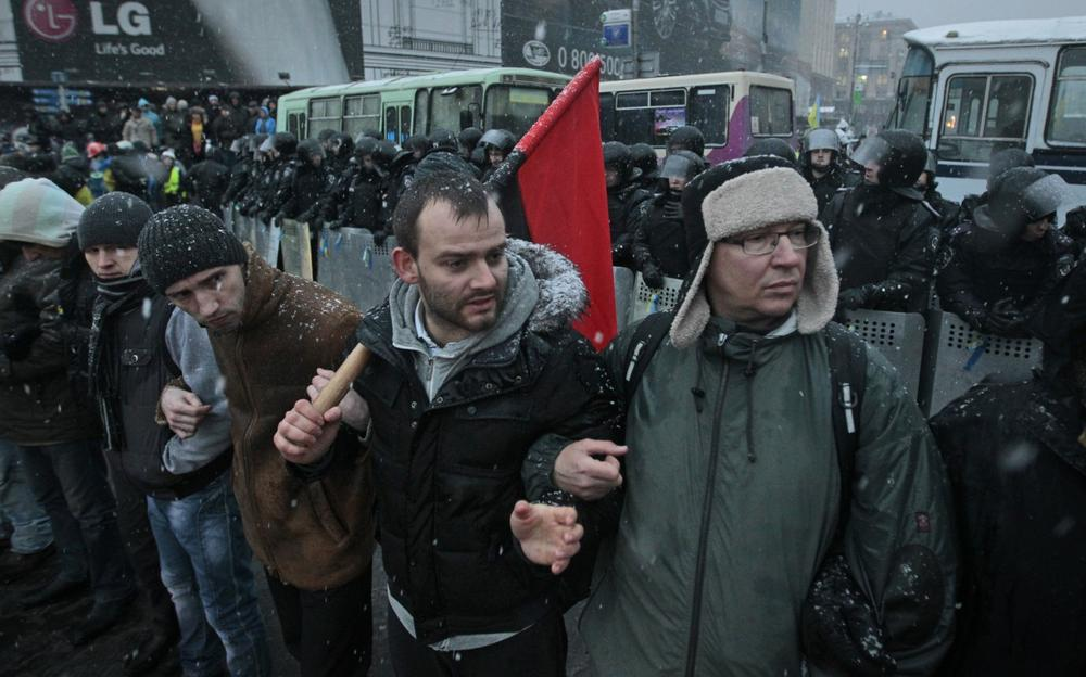 Pro-European Union activists stand with their backs towards police, in front of the police line to prevent provocations near the Independence Square in Kiev, Ukraine, Monday, Dec. 9, 2013. (Sergei Chuzavkov/AP)