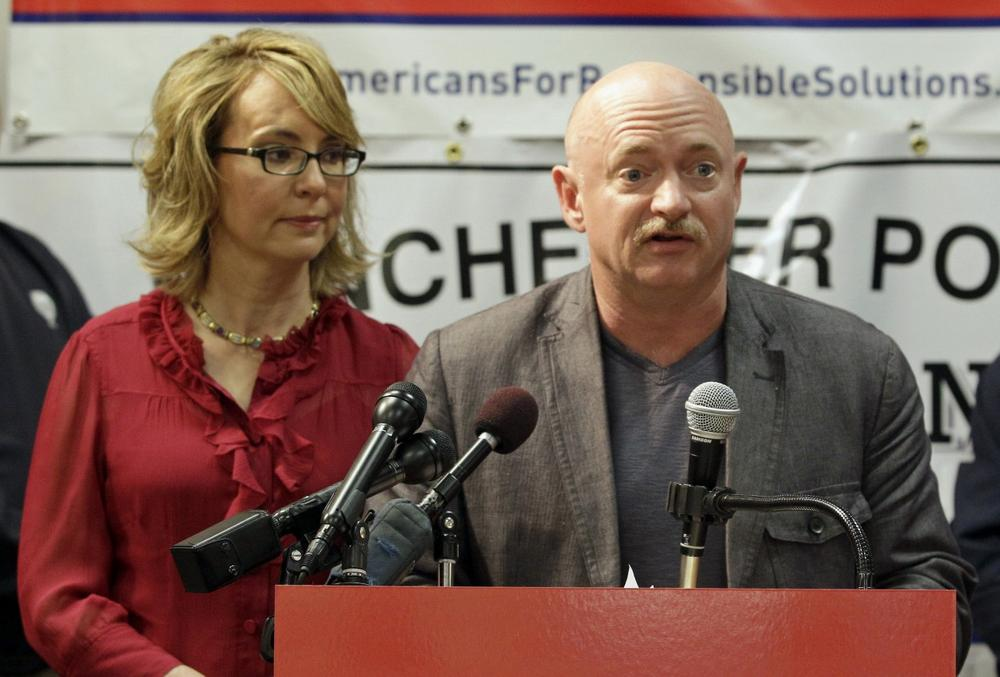 Former Arizona Rep. Gabrielle Giffords listens as her husband retired astronaut and combat veteran Captain Mark Kelly speaks during a news conference at the Millyard Museum, Friday, July 5, 2013 in Manchester, N.H. (Mary Schwalm/AP)